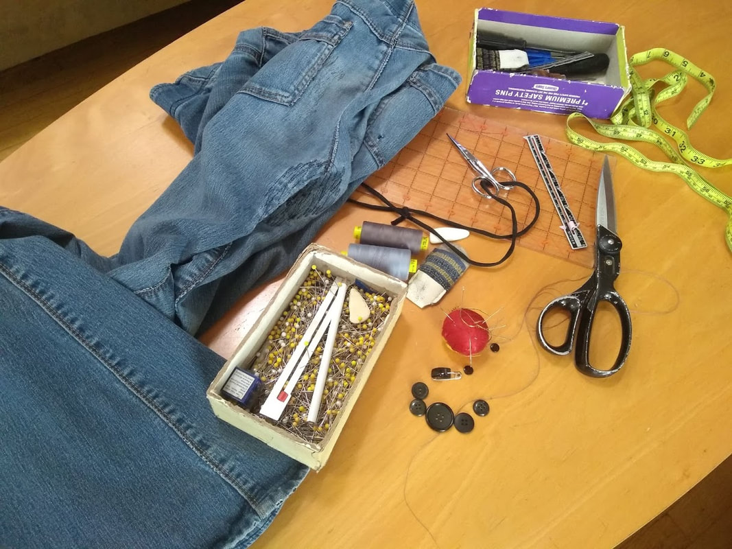 Mending and sewing supplies and a pair of heavily repaired blue jeans on a table