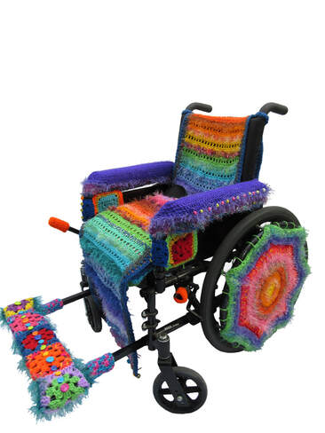 A manual wheelchair covered in colorful crocheted yarn