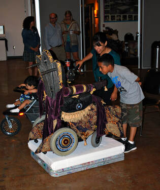 A group of people look closely at a wheelchair that is re-upholstered to look like a throne.