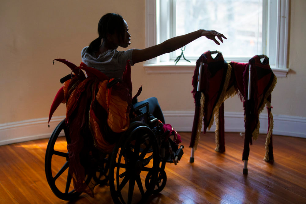 On the left is a dark haired, dark skinned woman in a wheelchair with orange and red tendrils peeking up from the back of the chair. On the right, a heavily fringed walker sits in front of an open widow.