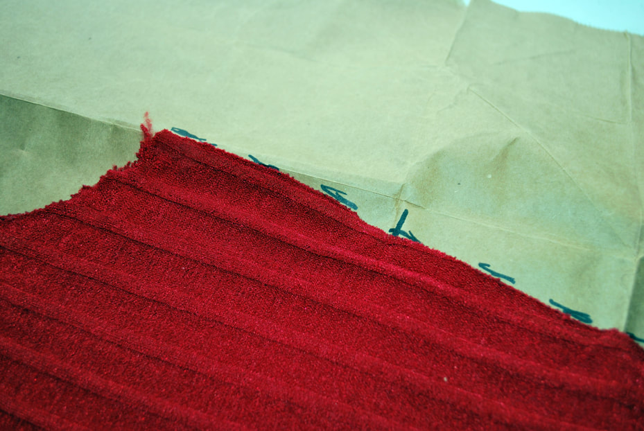 Tracing around the outside of the armhole and side seam of the red top. Cross marks are used to mark the shoulder seam and under bust lines.