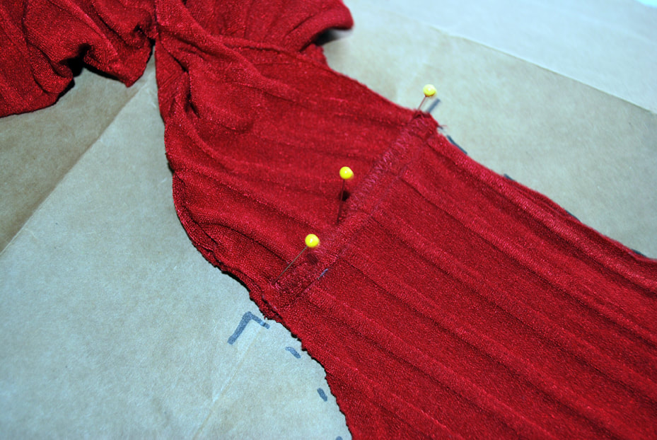 A well-pinned shoulder seam on the red top.