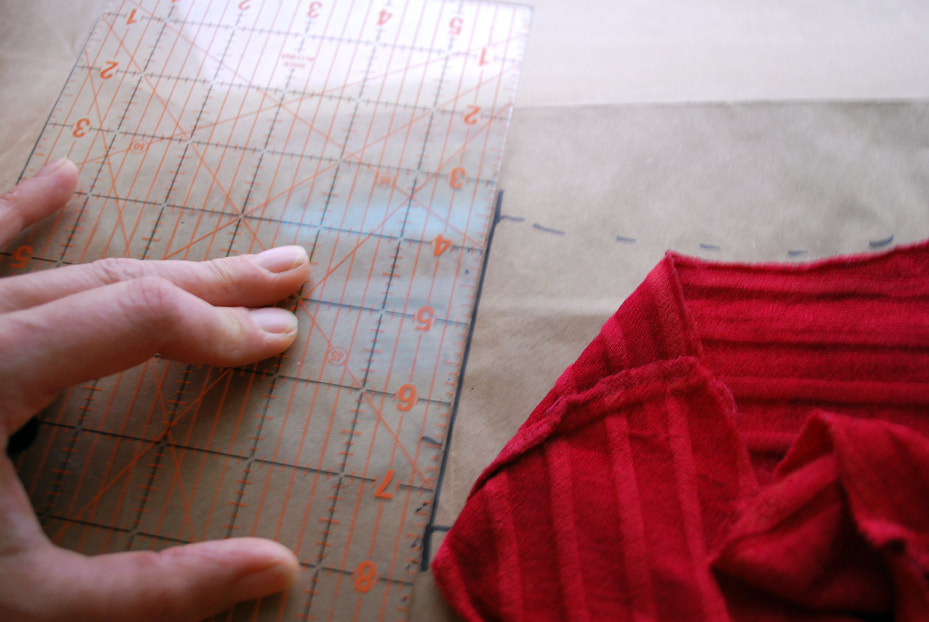Using a ruler as a guide to draw the shoulder seam line on the pattern paper.