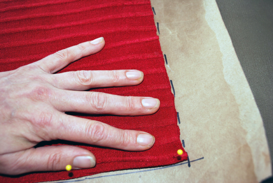 A hand holds the bottom of the panel to keep it smooth, and the other hand traces dotted lines around the bottom edge.