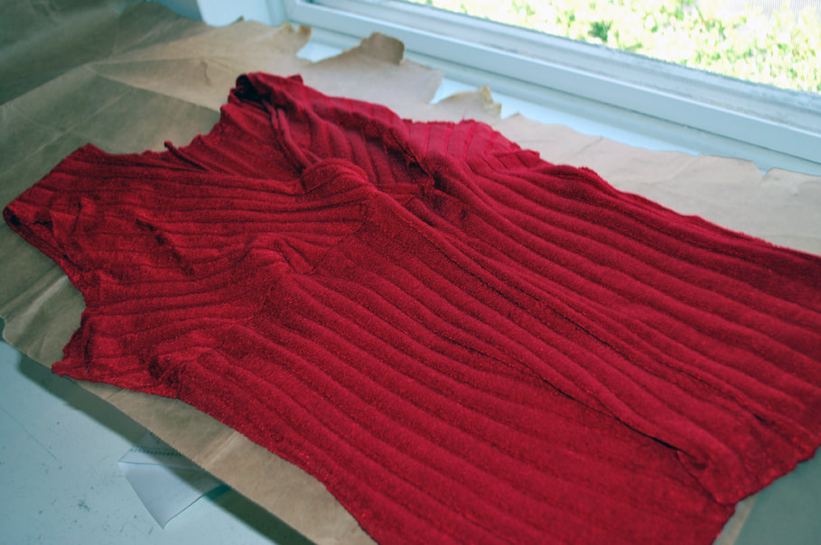 A red sleeveless blouse with its side seams unpicked sits on top of brown paper.
