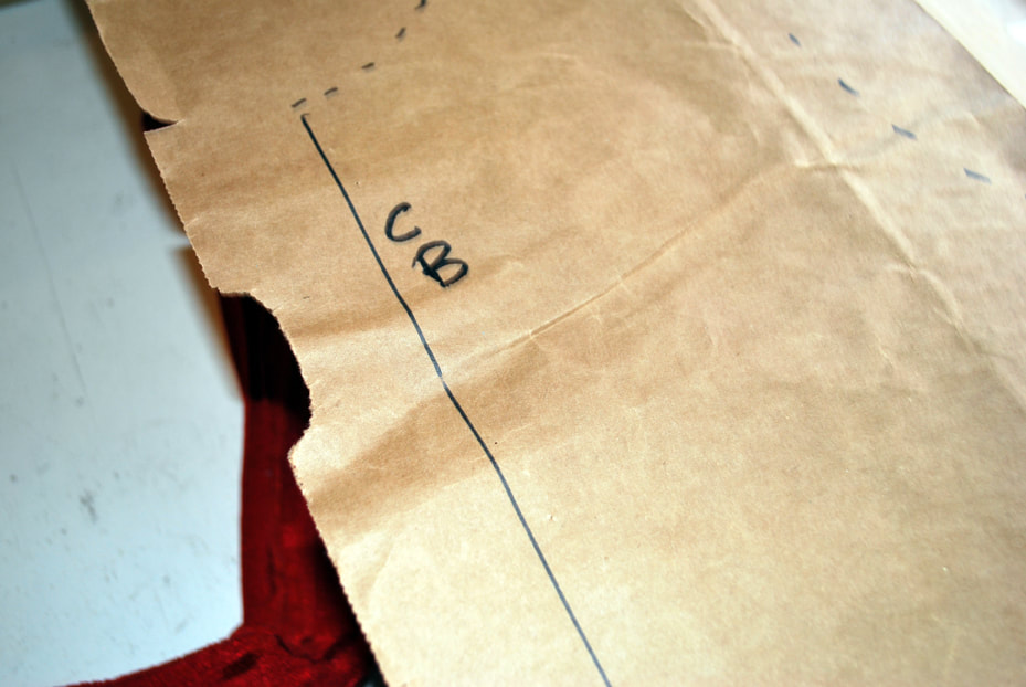 A brown paper pattern with the letters CB near a straight line at center back.