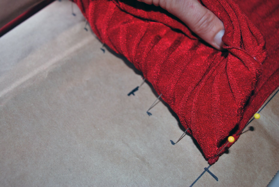 Pulling the bust fabric back down to clearly mark the overlap on the pattern with a cross mark.