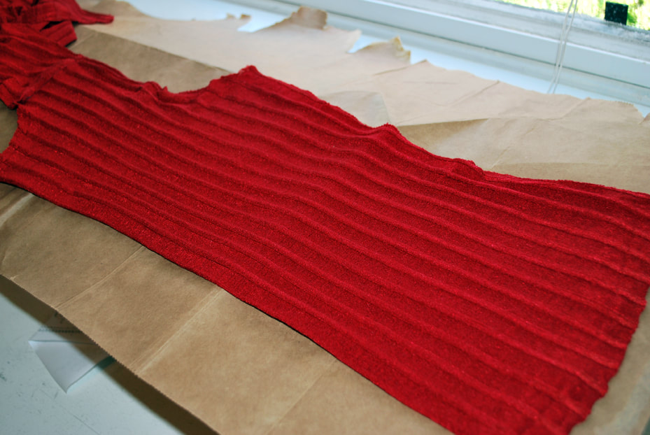 Back of the red top folded in half lengthwise.