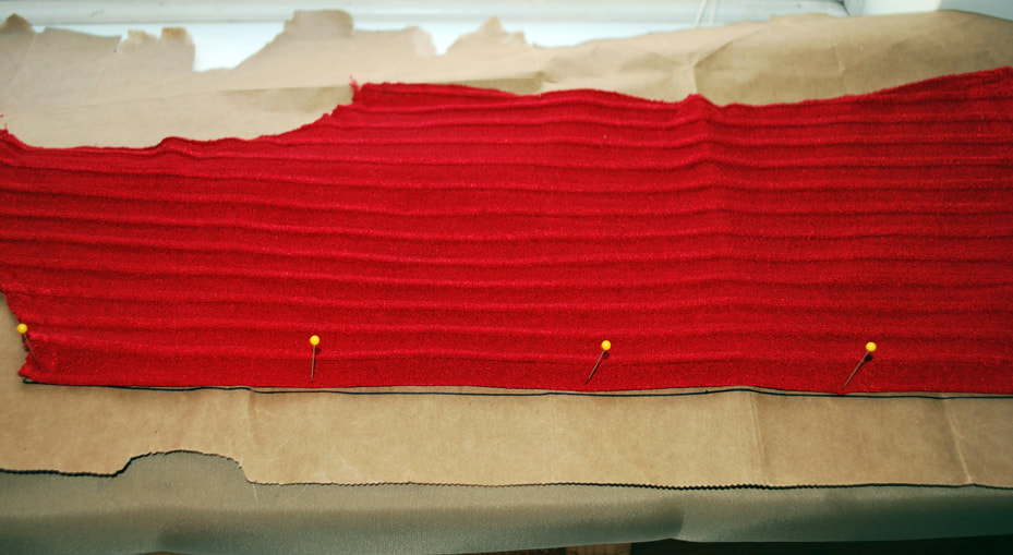 The back of a red top folded in  half with the folded edge pinned to a straight drawn-in line.