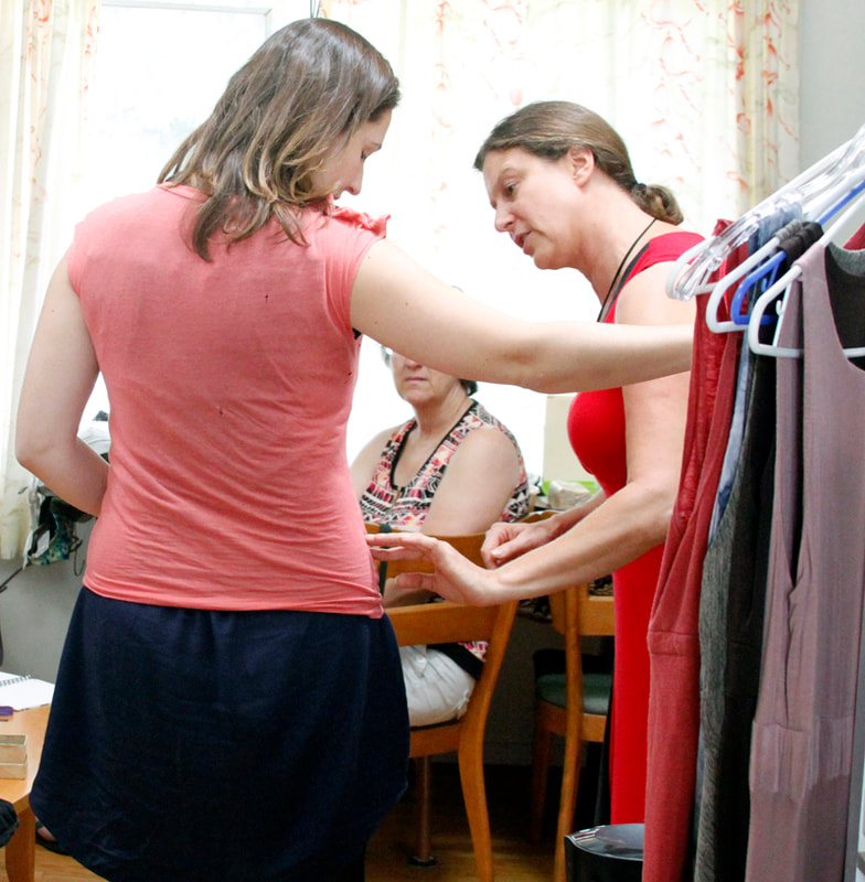 A woman with her back to us is being fitted into a pink t-shirt while a woman in red on the right points out the alterations.