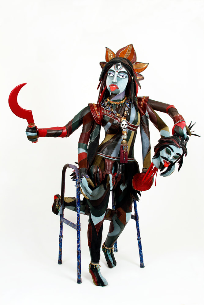 A sculpture representing the goddess Kali is built into a walker. The figure has 6 arms, 4 lower legs, and multi-colored skin. She holds a red scythe, a severed demon head, and a bowl.