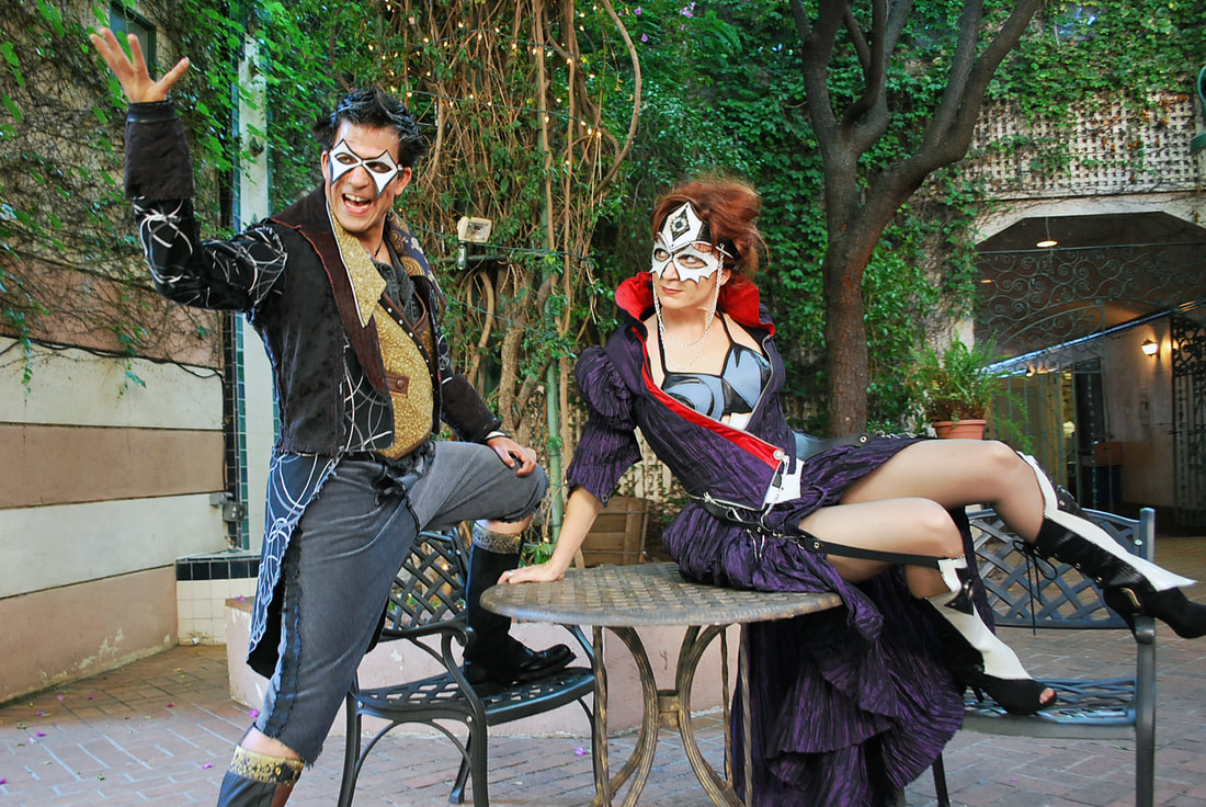 Two masked characters in colorful costumes tell stories around a cafe table in a wooded courtyard.
