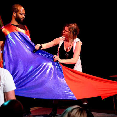 A dark skinned, bearded man with glasses wears a tent of shiny red and blue fabric. On the right, a light skinned woman in black and white staples the fabric around him.