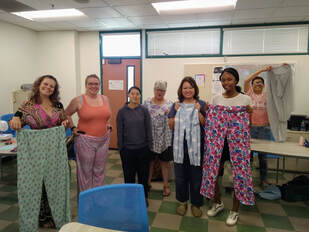 A diverse group of women hold up colorful pajama pants