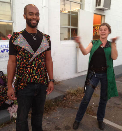 On the left, a bearded dark skinned man in glasses stands wearing a vest of chili print fabric. On the right is a woman in black with a long green vest smiling and waving her hands.