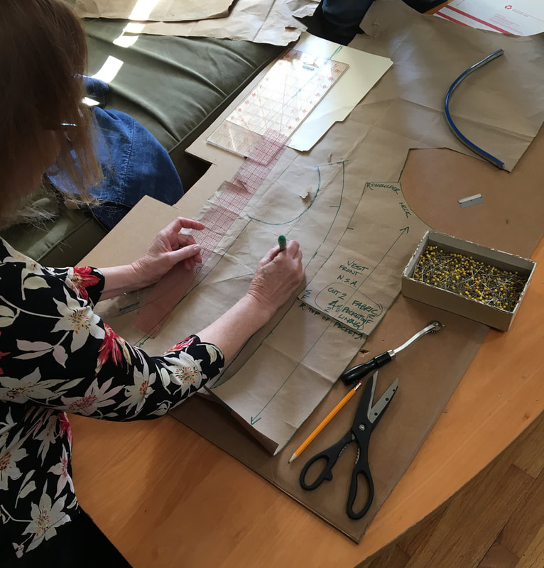 A pair of hands draft out a vest pattern onto brown paper.