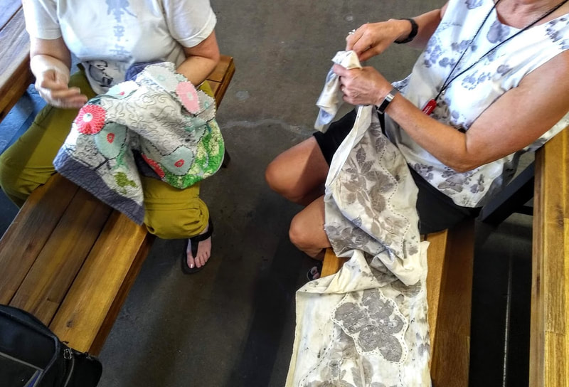Two people sitting on benches, hand sewing patches onto fabric runners.