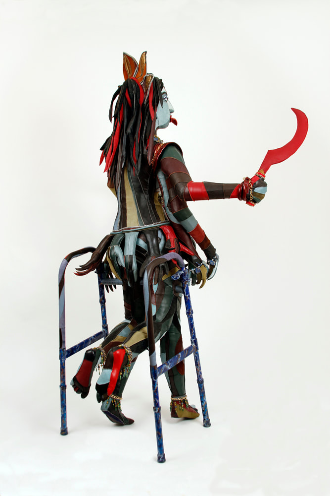 Back view of a sculpture representing the goddess Kali that is built into a walker. The figure has 6 arms, 4 lower legs, and multi-colored skin. She holds a red scythe in her top right hand.