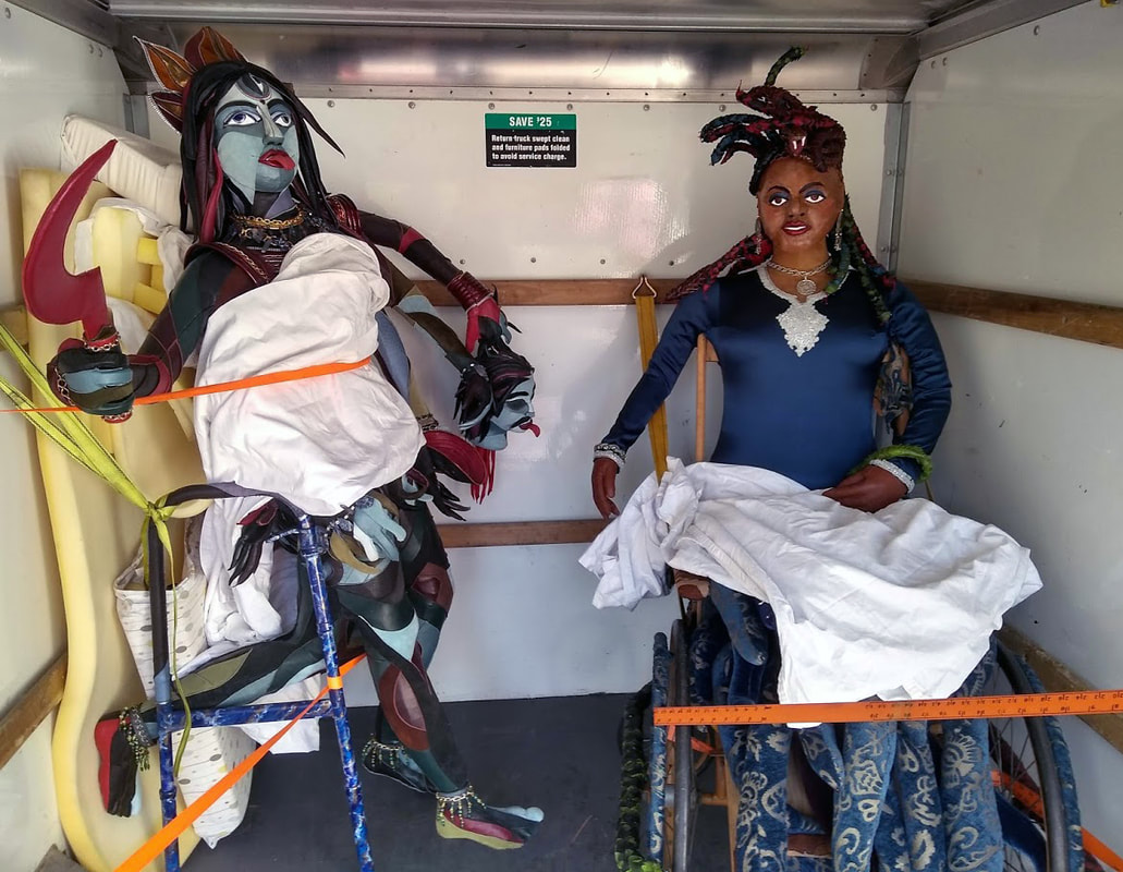 A sculpture of the goddess Kali built into a walker and a sculpture of Medusa built into a wheelchair are strapped into the back of a van and padded with sheets and foam.