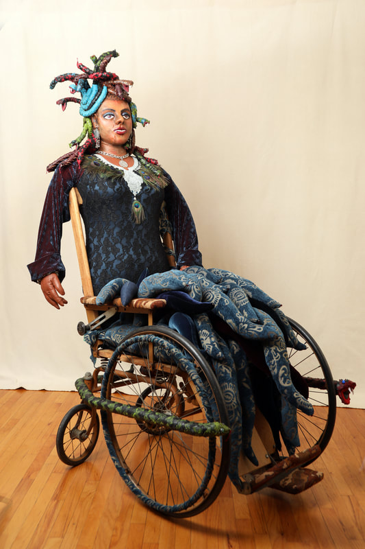 A sculpture of Medusa is built into the seat of a vintage wheelchair. The figure has snakes for hair, a peacock feather necklace, and a seat full of wave-like tentacles.