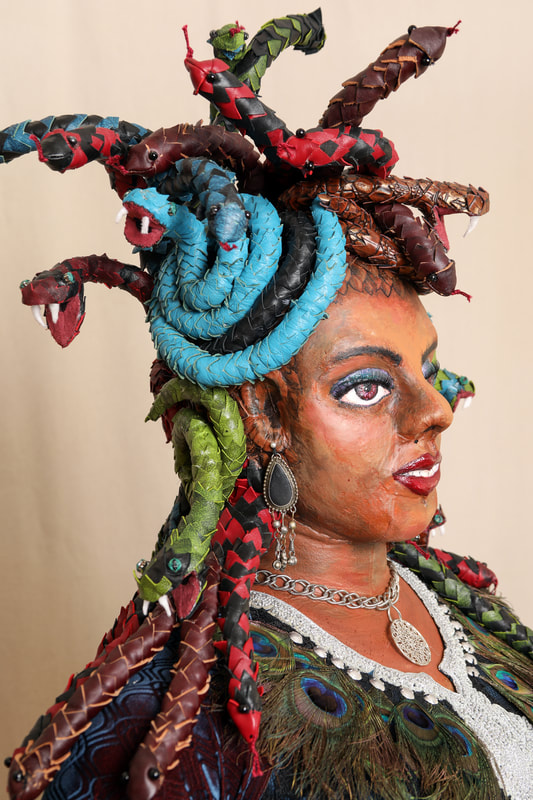 The head and shoulders of a Medusa sculpture, focused on the multi-colored leather snake hair, painted face, and silver and peacock feather necklace.