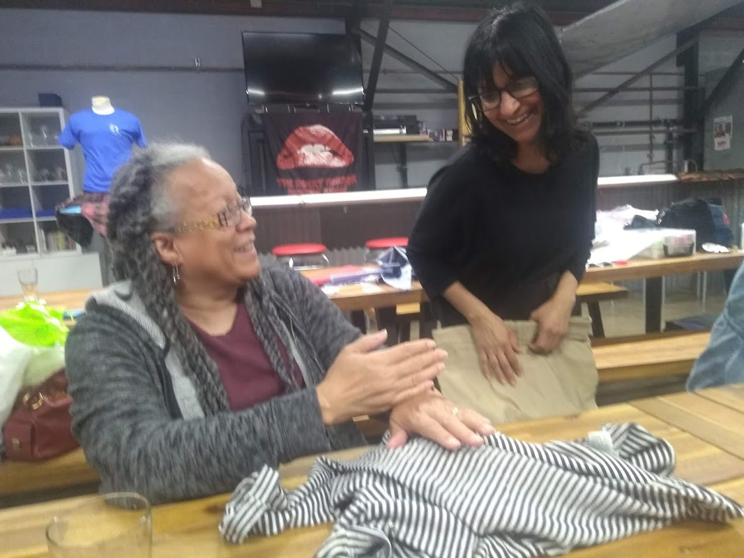 Two women in glasses are  working at a table. They are smiling and holding clothing to repair.