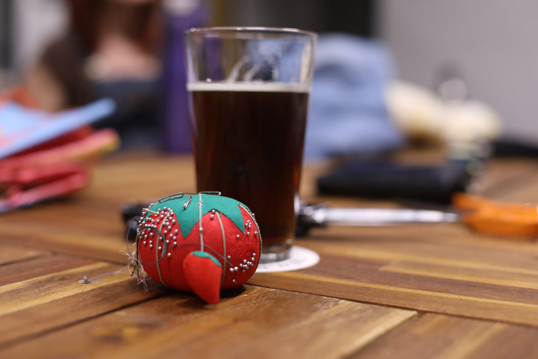 A pincushion, mostly full glass of porter, and a pair of scissors lay on a wooden table.