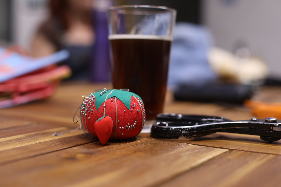 A tomato shaped pincushion and pair of scissors in front of a pint glass of porter