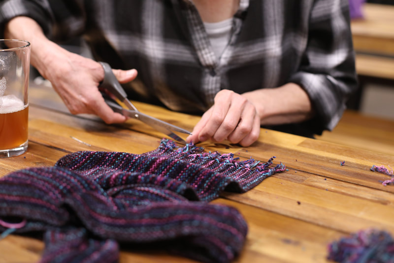 A pair of hands holding scissors trim the fringe on a purple, blue, and pink striped chenille scarf.