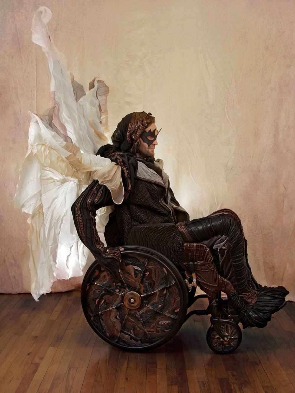 Right side view of a masked man in black, copper, and silver drives a wheelchair with a white and silver sail. The chair's wheels are covered in black, copper, and multi-colored metallic swirls.