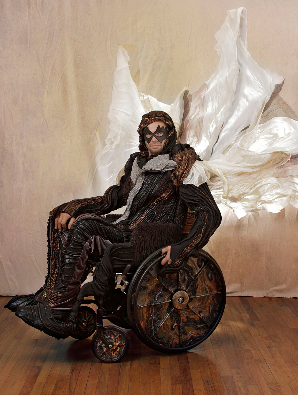 Left side view of a masked man in black, copper, and silver drives a wheelchair with a white and silver sail. The chair's wheels are covered in black, copper, and multi-colored metallic swirls.