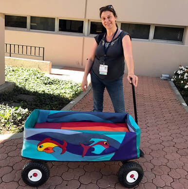 A light skinned woman in jeans and a t-shirt stands, holding the handle of a wagon dressed in a vinyl cover with brightly colored fish and waves.