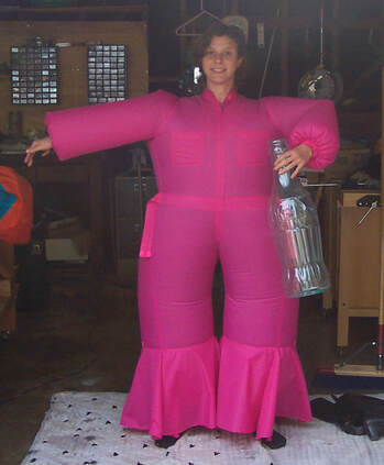 Woman in a bright pink inflatable jumpsuit holding an oversized soda bottle