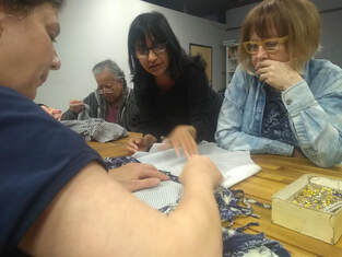 A diverse group of women work on mending.
