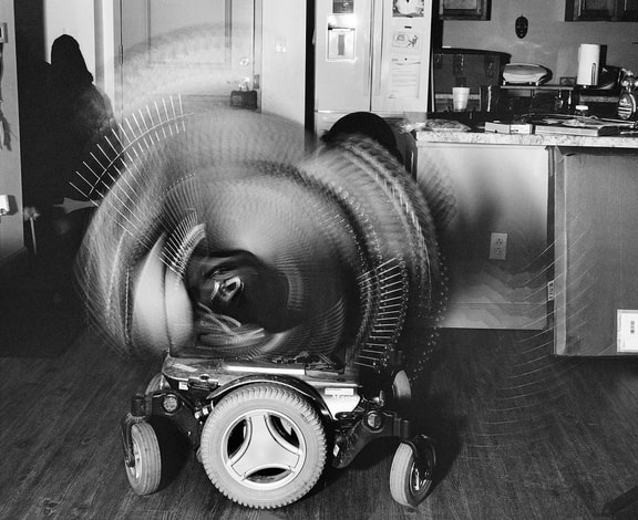 A black and white photo of a wheelchair base on a hardwood floor. Above the base, the chair tilts back and forth creating a blurred semi-circle. In the backgroun is a dark shadow of a figure on the left and kitchen counters on the right.