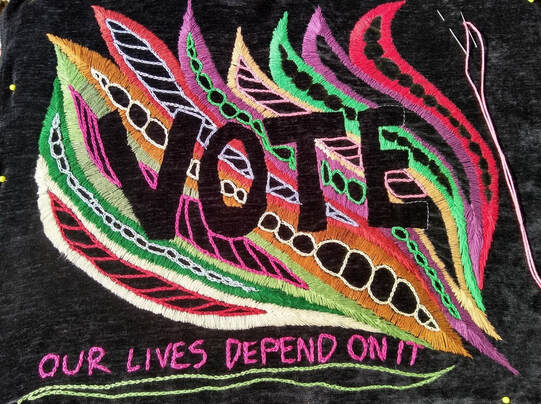 Colorful embroidery outlines the word VOTE in black. The words OUR LIVES DEPEND ON IT are embroidered in pin at the bottom.