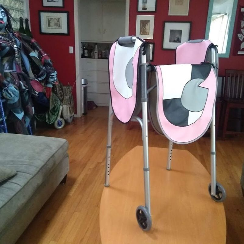 A classic aluminum walker with vinyl hangings in a graphic pink, white, black, and grey graphic design.