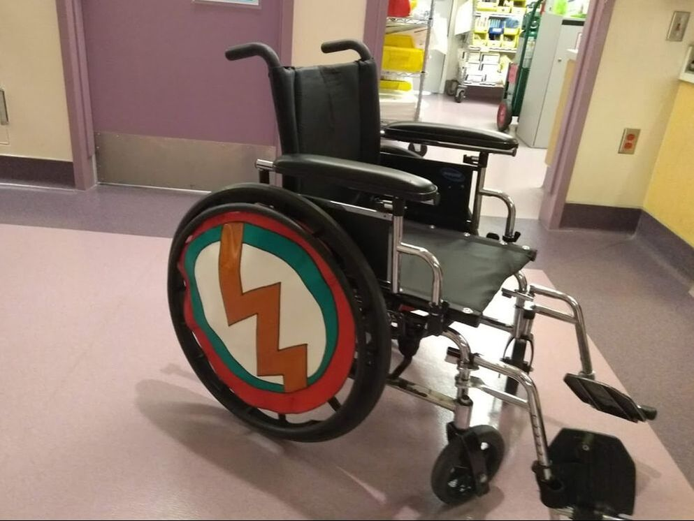 A classic manual wheelchair has a vinyl wheel cover in red, white, black, and green with a metallic orange lightening bolt down the center.