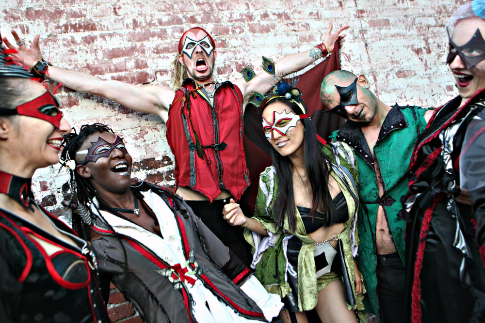 6 masked people in colorful costumes laugh and gesture in front of a brick wall.