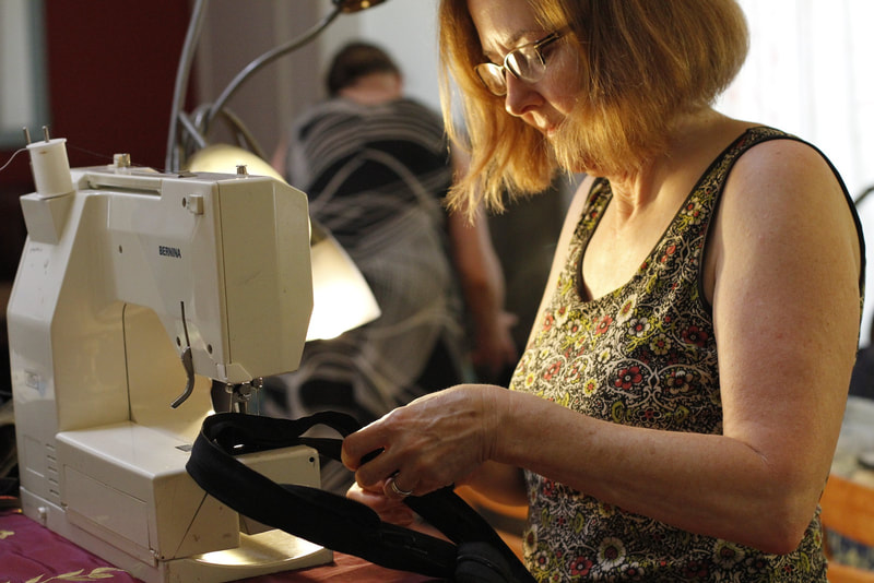 A woman in glasses sews zipper strands together on a sewing machine.